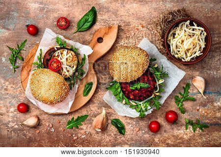 Fresh homemade two veggies burgers served on cutting board over stone vintage background. Vegan grilled eggplant arugula sprouts and pesto sauce burger. Veggie beet and quinoa burger. Top view overhead flat lay.