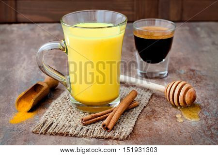 Turmeric golden milk latte with cinnamon sticks and honey. Detox liver fat burner immune boosting anti inflammatory healthy cozy drink