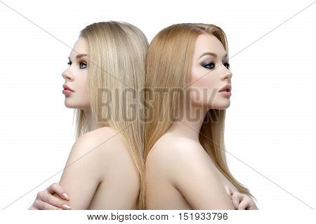 Two beautiful girls with long blond straight hair and bright makeup. Isolated over white background. Closeup studio beauty shot.