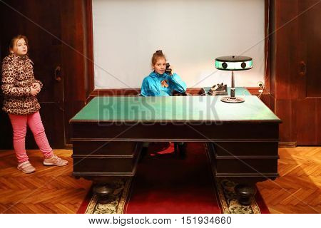 SAMARA, RUSSIA - MAY 8, 2015: Girl sitting at table and holding phone and her friend stands (models with releases) in Stalins bunker
