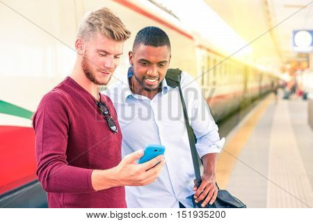 Interracial couple of men looking mobile phone screen at train station - Handsome guys commuters with casual clothing using smartphone at railway platform - Concept of everyday urban lifestyle