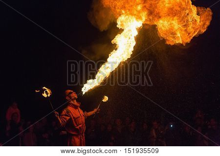 PRAGUE CZECH REP - OCTOBER 15 2016: Man fire-eater blowing a large flame from his mouth ( man spits fire)
