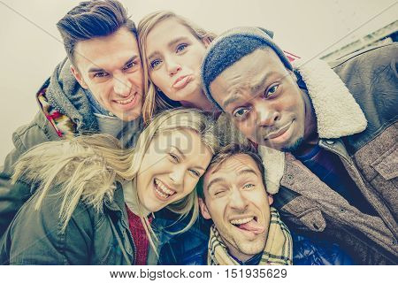 Best friends taking selfie outdoor on autumn winter clothes - Happy youth concept with multiracial people having fun together - Cheer and friendship against racism - Vintage lomo desaturated filter