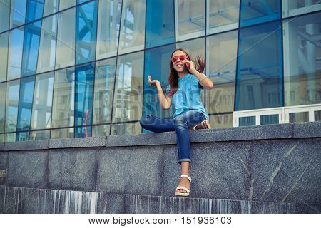 Excited and positive girl in lovely casual outfit has rather lively conversation on her smart phone while sitting on the concrete bench against the business center in the downtown