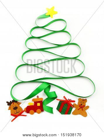 A cutout yellow star sits atop a swirling green ribbon that curls into a Christmas tree shape with felt cut out presents underneath on a white background