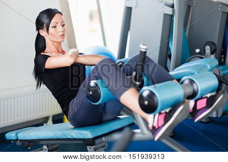 Long hail brunette doing crunch on bench.