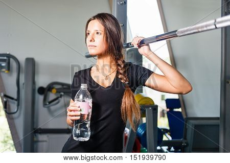 Girl with a water bottle in a gym.