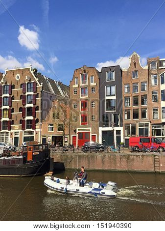 AMSTERDAM, NEDERLANDS - MAY 4, 2016: People enjoy a boat ride in the canals of Amsterdam in sunny day. Amsterdam is the capital and most populous city of the Netherlands. Vertical image.