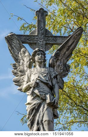 Grave Angel figurine on top of grave at christianity cemetery