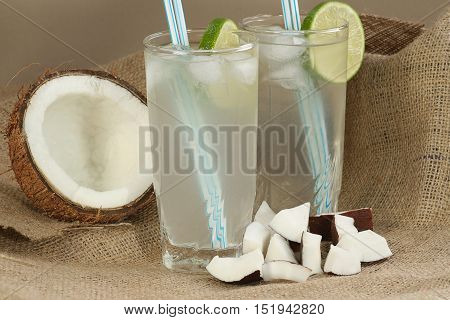 two tall glasses of fresh coconut water with ice and lime