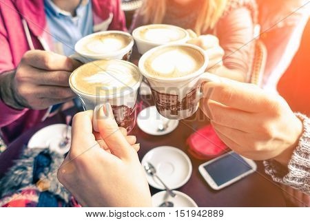 Group of friends cheers with cappuccino cup in cafe bar with phone on table - Family having fun drinking together at restauran in winter season closeup scene with soft vintage filter