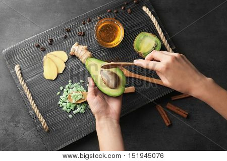 Female hands holding avocado and natural ingredients for facial mask on wooden board and grey background