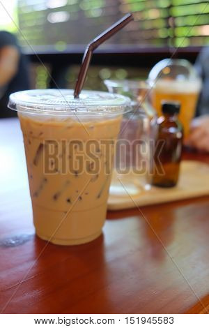 Iced coffee latte in take away cup on wood table