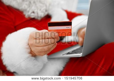 Santa Claus with credit card and laptop, close up