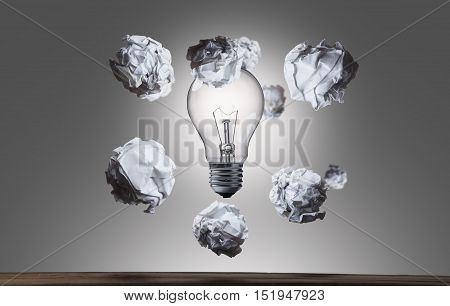 crumpled paper balls flying arround light bulb brainstorming in the office concept