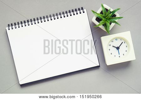 Top view of office desk table with open spiral notebook white alarm clock and small plant in a white pot