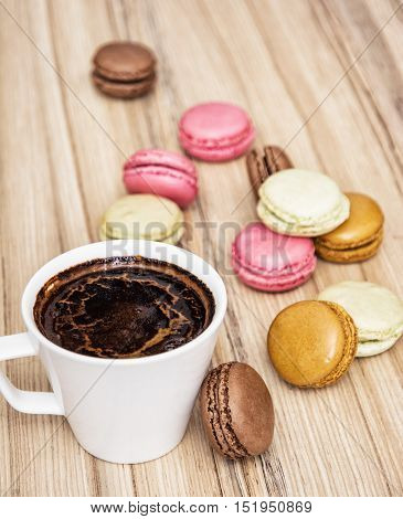 Cup of black coffee with french colorful macarons. Sweet delight. Sweet food and drink. Tasty macarons. Vertical composition.