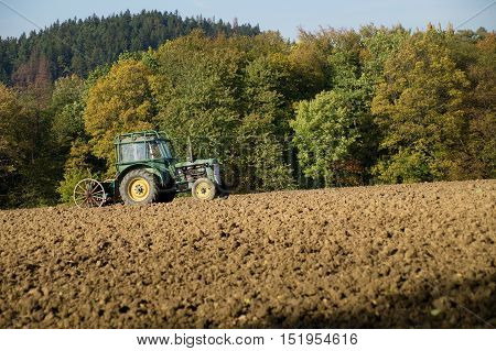 Farmer using an old tractor ploughing field