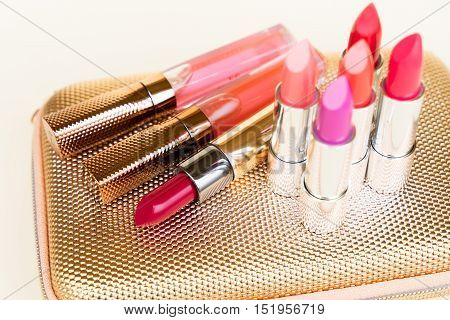 Collection of colorful lipsticks on golden woman pursue bag