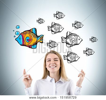 Blond woman with crossed fingers is standing against gray wall with fish sketches. One fish is colored and swims in different direction. Concept of original approach to problem solving.