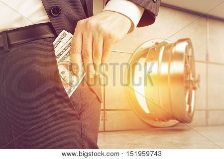 Close up of businessman putting several dollar notes into his pocket while standing against slightly open vault door. 3d rendering. Toned image