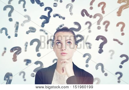 Close up of thoughtful young woman with her hand on the chin standing in room full of floating question marks. Concept of solution finding. Toned image