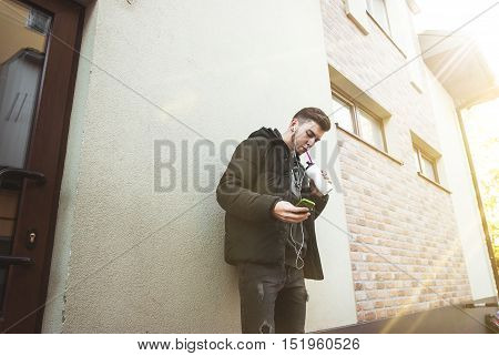 Cute young boy in jacket drinkers drink and listen to music. Uses phone. Sunny day. Funny mood.