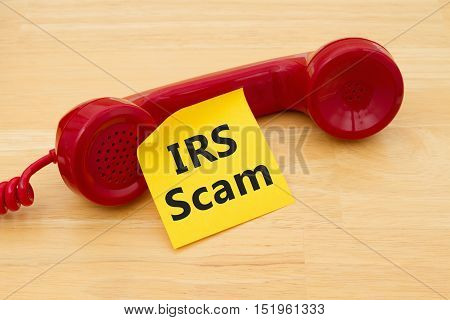 Getting a call that is an IRS Scam A retro red phone with yellow sticky note on a desk with text IRS Scam