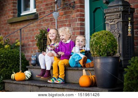 Group of little children sitting on stone stairs to the house door on warm autumn day during Halloween or Thanksgiving time. Kids playing in the front yard in fall. Home porch decorated with pumpkins.