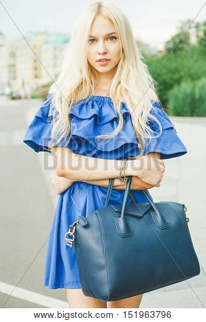 Outdoor summer smiling lifestyle portrait of pretty young woman with big blue handbag and hi heels shoes. Long blond hairs, blue outfit in park. Girl, style and fashion.