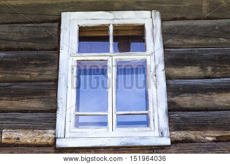 Old window with glass with a blue sky on the background of the wooden wall of the countryside log house.