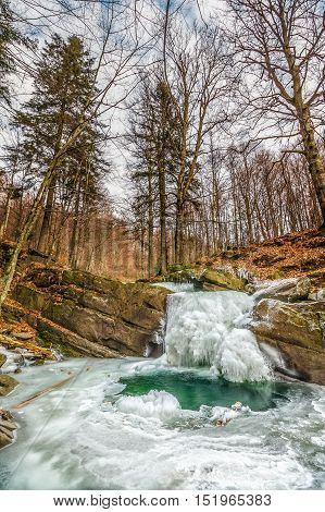 Frozen Waterfall Abow The Huge Boulder In Empty Forest