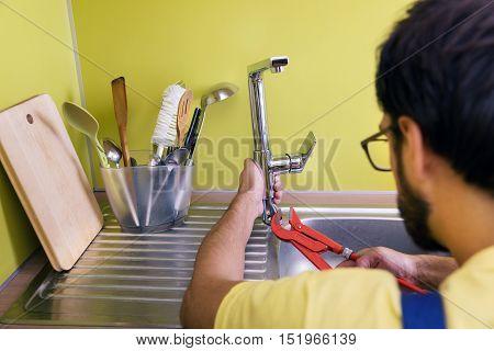 plumber installing repairing water tap in kitchen