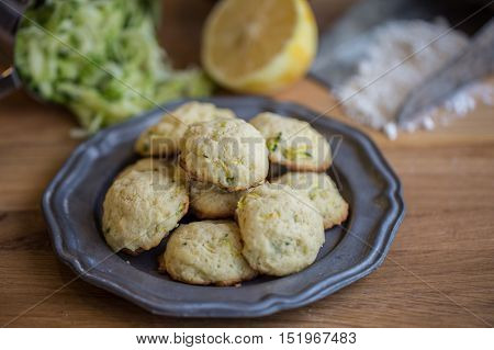 Lemon cookies on a pewter plate with ingredients in the background