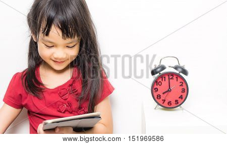 Asian girl is holding an alarm clock that count for lunch time. Little Asian girl is very happy to get a lunch break. Asian girl is smiling and holding an alarm clock counting down to 12.