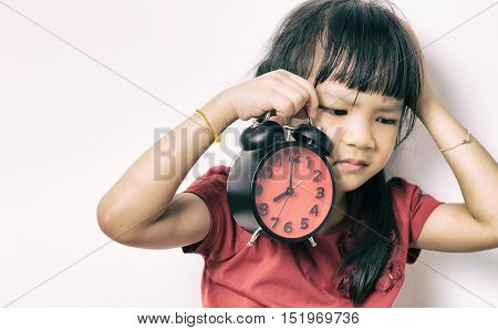 Little asian girl is angry at the alarm clock for waking her up. A kid in red shirt is upset that the alarm clock wake up her so early. Lazy Japanese girl doesn't want to get up in the morning.