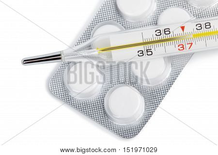 Close-up traditional thermometer with pills on white background. Background isolated image focus on thermometer