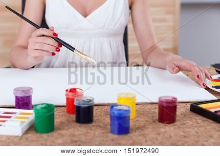 Close up of woman painter's hands holding a brush and starting to paint on large sheet of paper. Concept of creative work
