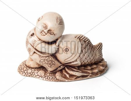 Netsuke of the boy with big fish. Isolated. A miniature sculpture which was used as a button-like trinket in traditional Japanese clothes kimono kosode which was devoid of pockets.