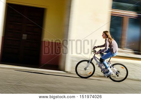 Teenage Girl Bicycling In Roller Boots. Speed Shooting