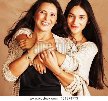 cute pretty teen daughter with mature mother hugging, fashion style brunette makeup close up tann mulattos, warm colors, lifestyle real people concept