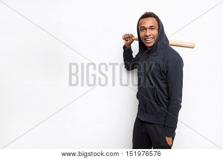 Smiling African American man leaning at white wall and holding baseball bat. Concept of training and sports. Mock up