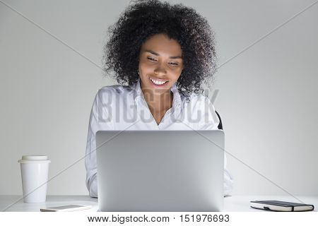 Close up of smiling office employee sitting at her workplace with laptop in room with gray walls. Concept of high spirits