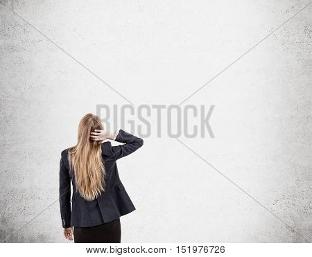 Woman scratching her head is standing near blank concrete wall and looking at it. Concept of tabula rasa. Mock up