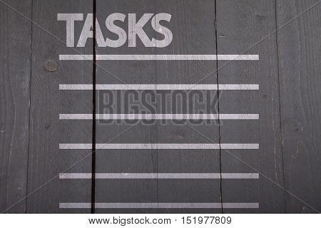 White tasks list on black wooden background