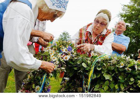 Mariefred, Sweden - June 24, 2016: Two elderly women in traditional costumes attach one of the garlands on the maypole before the rising of the rod at the tradidionellt public midsummer celebration.