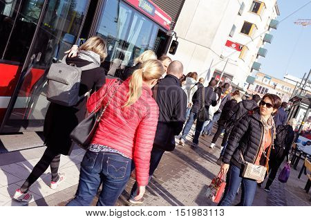 Stockholm, Sweden - May 7, 2015: Passengers have disembarked oncoming bus and walks towards Liljeholmen metro station at rush hour.