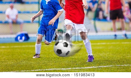Youth soccer league.Training and football match between youth soccer teams. Running football players kicking ball.
