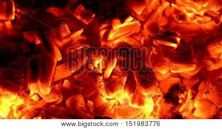 The burning glowing embers on the fire.