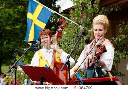 Mariefred, Sweden - June 24, 2016: The musicians Lena Oden (left) and Agnes Oden (right) plays wearing traditional costumes at the traditional public Swedish midsummer celebrations organized in Mariefred.